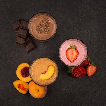 Вид сверху ассортимента молочных коктейлей с фруктами и шоколадом