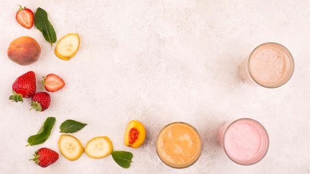 Вид сверху ассортимента молочных коктейлей с фруктами и копией пространства