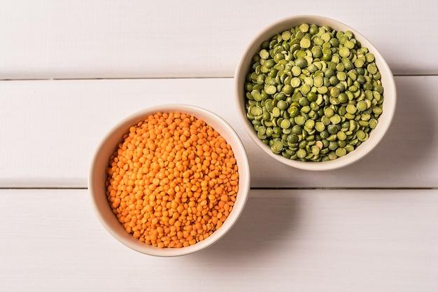 白い木製のテーブルの上のエンドウ豆、レンズ豆、豆、豆類の品揃えの平面図です。