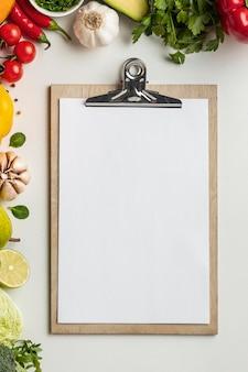 クリップボードと野菜の品揃えの上面図