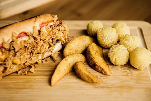 Вид сверху на ассортимент картофеля. запеченный жареный картофель на деревянной тарелке, подается с томатным соусом. дольки чипсов, картофельные крокеты-пюре, шарики в панировке и во фритюре.