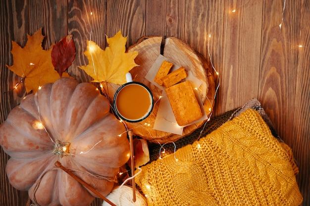 カップパンプキンパイとセーターパンプキンジュースと甘い焼きたての秋の構成の上面図...