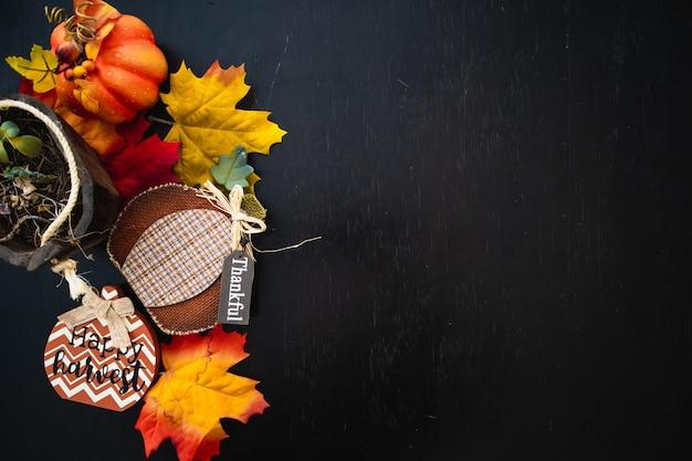 가을 단풍의 상위 뷰는 검은 나무 표면에 호박과 나뭇잎