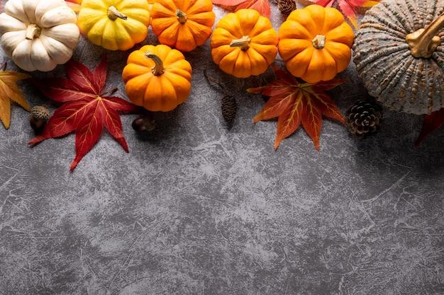 Вид сверху осенних кленовых листов с тыквой на сером бетонном фоне.