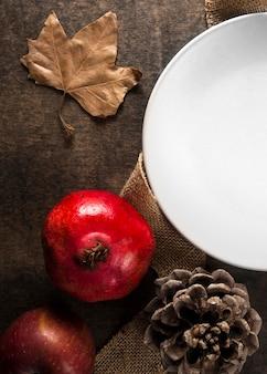 Вид сверху осеннего граната с тарелкой и сосновыми шишками