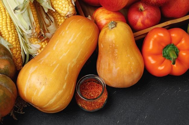 Вид сверху осенней овощной композиции с тыквами и яблоками на черном