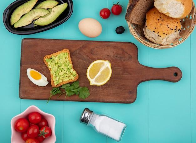 Вид сверху мякоти авокадо с поджаренным ломтиком хлеба на деревянной кухонной доске с ломтиками лимона и помидорами на синем