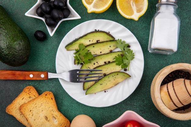 Вид сверху ломтиков авокадо на белой тарелке с вилкой с черными оливками, лимоном, солонкой на gre