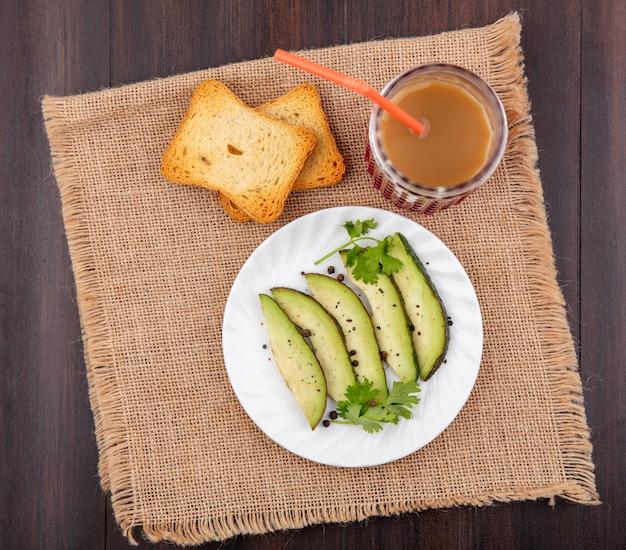 木の袋の布のグラスにジュースとパンのトーストしたスライスと白いプレート上のアボカドスライスのトップビュー