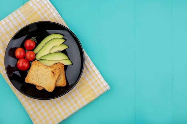 Вид сверху ломтиков авокадо с помидорами, поджаренных ломтиками хлеба на черной тарелке на желтой клетчатой скатерти на синем