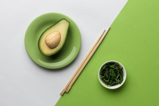 Вид сверху авокадо с миской зелени и палочек для еды
