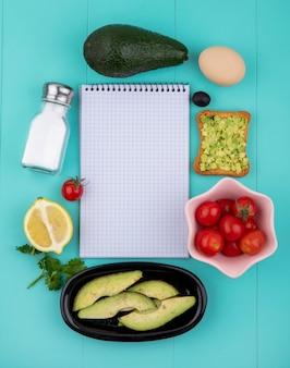 Вид сверху авокадо с яйцом, ломтиком жареного хлеба с оливковым маслом и мякотью авокадо с лимоном