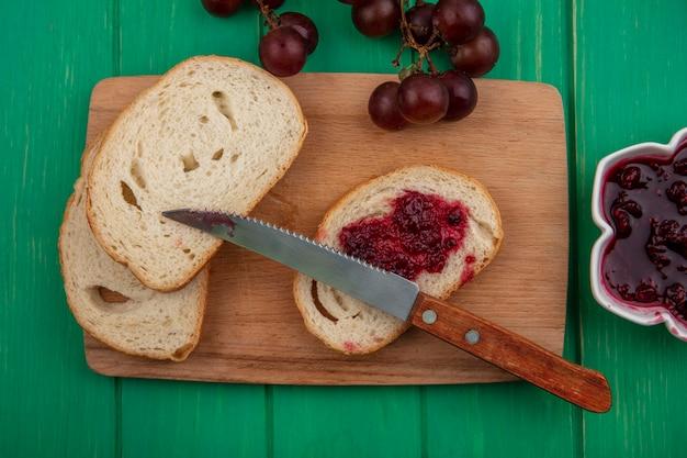 まな板にナイフでラズベリージャムを塗ったバゲットスライスと緑の背景にラズベリージャムのボウルとブドウの上面図