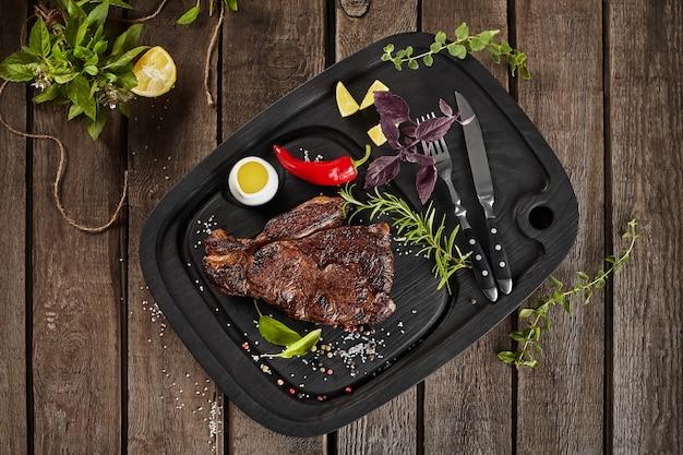 나무 표면에 양념과 구운 쇠고기 스테이크의 상위 뷰