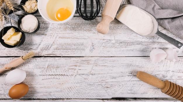 흰색 나무 테이블에 주방 장비와 구운 재료의 상위 뷰