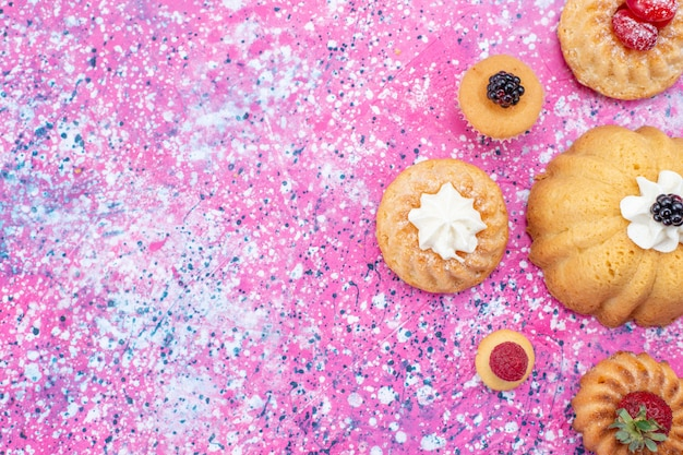 明るい紫色の机の上のベリーと一緒にクリームと一緒に焼いたおいしいケーキ、ケーキビスケットベリー甘い焼き茶の上面図