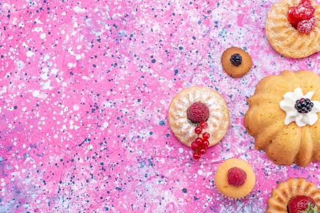 明るい紫色の机の上のベリーと一緒にクリームと一緒に焼いたおいしいケーキ、ケーキビスケットベリーの甘い焼きの上面図