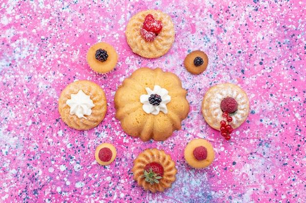 明るい紫色の机の上にさまざまなベリーと一緒にクリームと一緒に焼いたおいしいケーキ、ケーキビスケットベリー甘い焼き茶の上面図