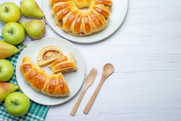 ガラス板の内側に形成された焼きたてのおいしいペストリーバングルと白い机の上のリンゴと梨、ペストリービスケットの甘い焼きクッキーの上面図
