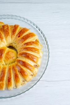 軽いペストリービスケットの甘い焼き砂糖の上に形成された焼きたてのおいしいペストリーバングルの上面図