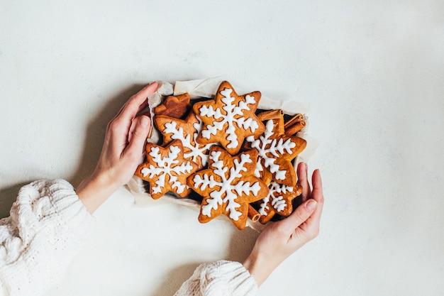白い表面に女性の手で保持されているボックスでジンジャーブレッドクッキーを焼く上面図