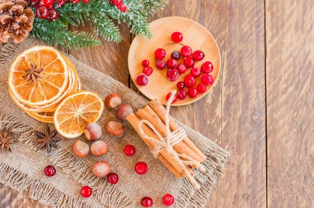 베이킹 재료의 상위 뷰입니다. 마른 오랑스, 계피 스틱, 아니스 별, 크랜베리가 나무 탁자 위에 있습니다. 복사 공간이 있는 크리스마스 향신료.