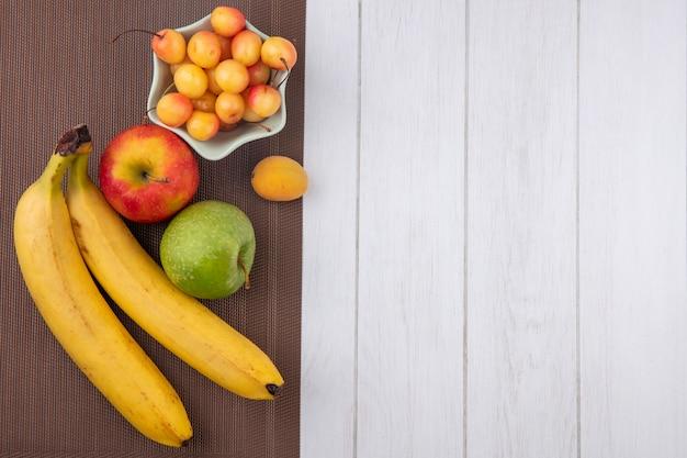 Вид сверху бананов с яблоками и белой вишней на коричневой салфетке на белой поверхности