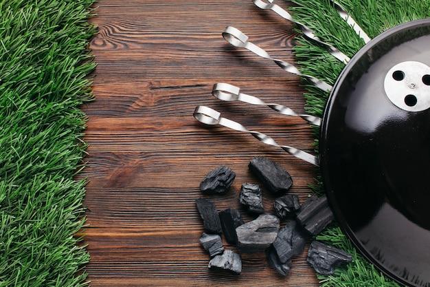 잔디 매트에 바베 큐 꼬치와 석탄의 상위 뷰