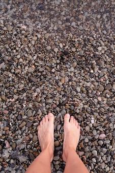 Вид сверху босых женских ног на пляже из гальки