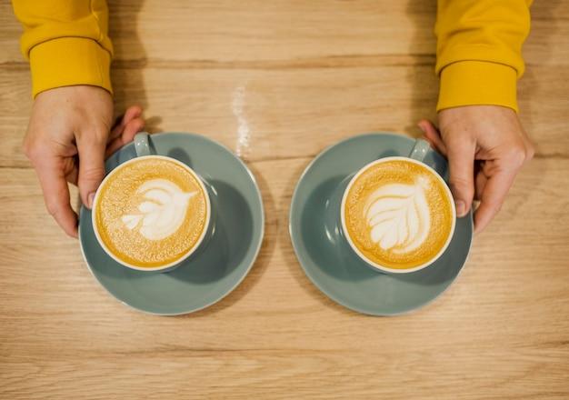Вид сверху бариста с двумя чашками кофе