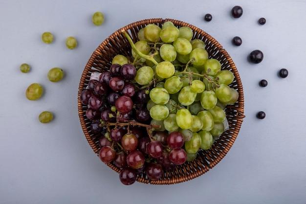 灰色の背景にブドウとブドウの果実のバスケットのトップビュー