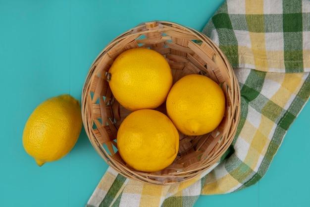 Вид сверху корзины лимонов на клетчатой ткани на синем фоне