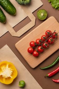 Вид сверху корзины органических овощей с продуктовым пакетом