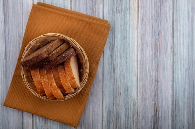 コピースペースを持つ木製の背景の布にライ麦と無愛想なものとしてスライスされたパンのバスケットのトップビュー