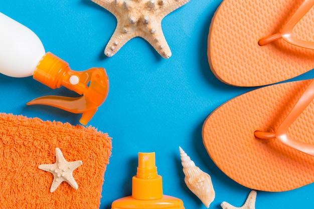 ビーチフラットレイアクセサリーの上面図。貝殻、ヒトデ、タオル、フリップフロップが付いた日焼け止めボトル。
