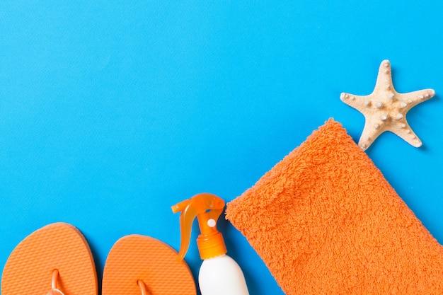 Вид сверху на пляжную квартиру лежал аксессуар. солнцезащитный крем бутылка с ракушками, морскими звездами, полотенцем и шлепанцем на цветном фоне с копией пространства