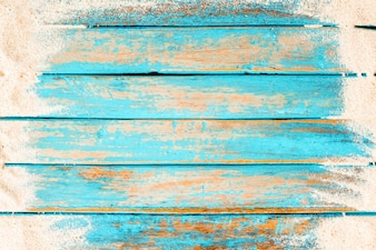 Top view of beach sand on old wood plank in blue sea paint background