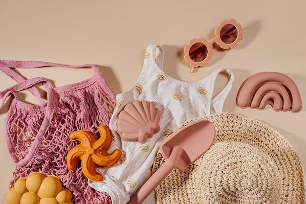 子供のためのビーチサマーアクセサリーの上面図。ファッション水着、サングラス、帽子、ビーチおもちゃ。休暇のためのモダンなセット。フラットレイ
