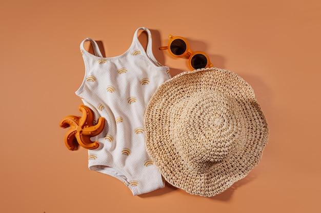 子供のためのビーチサマーアクセサリーの上面図。子供のためのファッション水着と帽子。フラットレイ