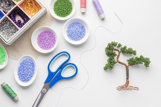 Вид сверху на принадлежности для работы с бисером с ножницами и деревом