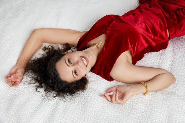 빨간 벨벳 양복을 입고 침대에 누워 카메라를 바라보는 아름다운 곱슬머리 젊은 여성의 상위 뷰