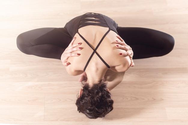 아름다운 여성의 뒷모습. 검은 옷을 입은 체조 선수는 손을 앞으로 구부리고 다리를 쭉 뻗고 앉아 훈련 전 워밍업