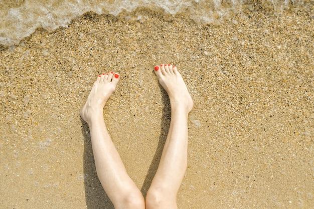 Вид сверху красивых женских ног с ярко-красным педикюром на песке пляжа.