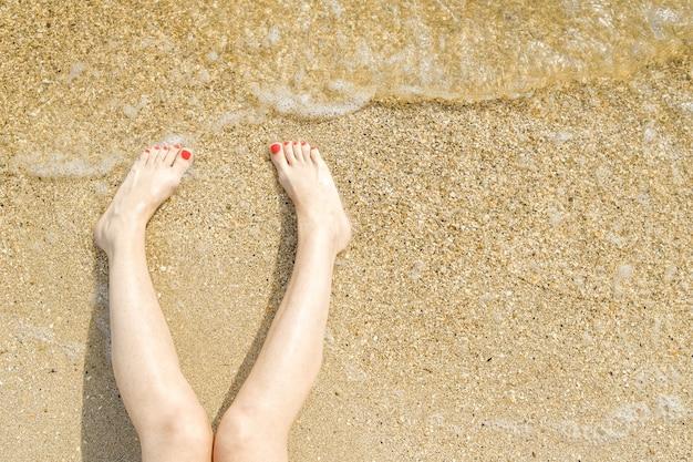 Вид сверху красивых женских ножек с ярко-красным педикюром на песке пляжа в морской воде