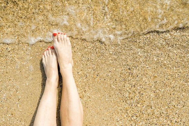 Вид сверху красивых женских ножек с ярко-красным педикюром на песке морского пляжа