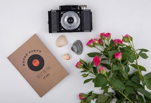 白い背景の上のカメラと葉を持つ美しい新鮮なピンクのバラの上面図