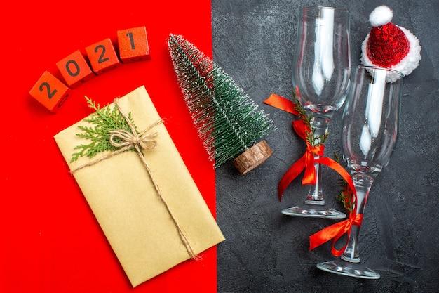 빨간색과 검은 색 배경에 아름다운 선물 크리스마스 트리 번호 산타 클로스 모자의 상위 뷰