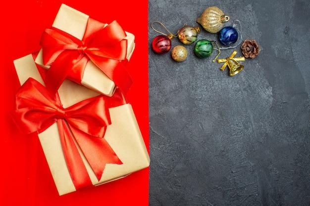 Вид сверху красивых подарков с аксессуарами для украшения ленты в форме банта на красном фоне