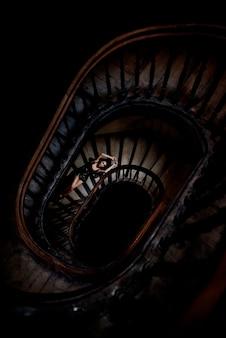 Вид сверху красивой девушки, которая лежит на темной круглой лестнице, почти голая
