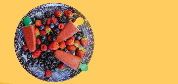 라스베리, 블루 베리, 딸기와 수제 베리 아이스크림 (셔벗)과 함께 아름다운 접시의 상위 뷰. 노란색 배경. 배너.